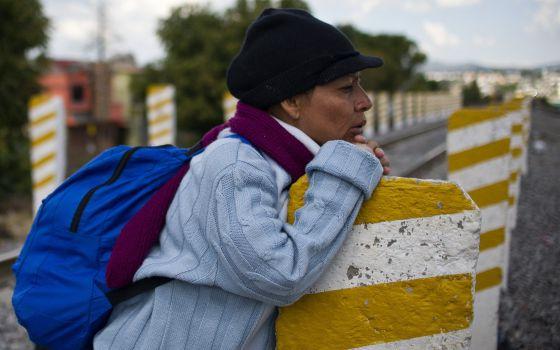 Uma imigrante centro-americana espera o trem de mercadorias conhecido como 'O Monstro' para chegar aos EUA, em Apizaco, estado de Tlaxcala, México.