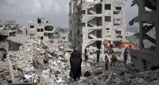 Una mujer palestina camina entre los escombros de las casas en Gaza.