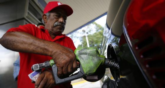 Un hombre llena de combustible un coche en Caracas.