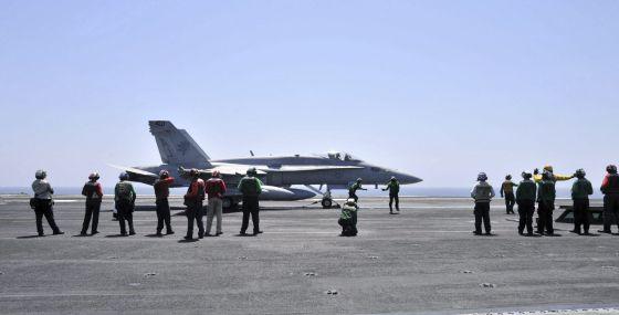 Miembros de la Marina de EE UU guiando a un avión Hornet FA 18