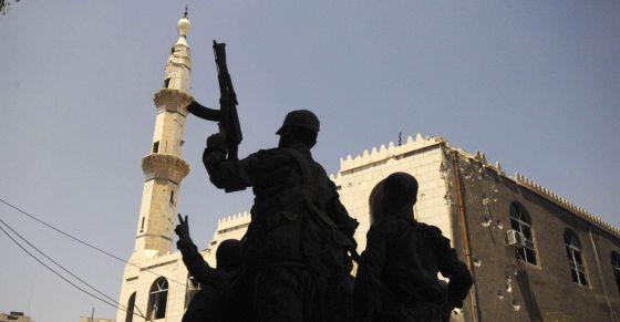Fuerzas leales a Bashar el Assad levantan sus armas en señal de victoria en Mleiha, cerca del aeropuerto de Damasco.