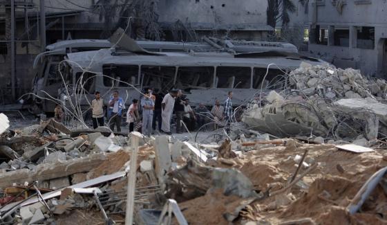 Un grupo de palestinos observan los restos de un edificio tras el bombardeo de Israel a Gaza, el pasado lunes.