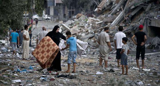 Una mujer lleva sus pertenencias con la ayuda de un niño en Gaza.