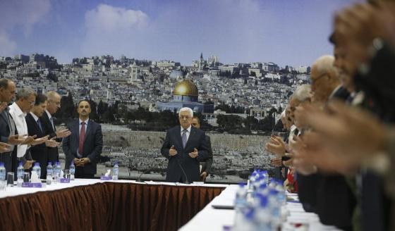El presidente Abbas, en el centro, lee el Corán antes de una reunión en Ramala, Cisjordania, el 26 de agosto