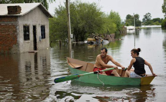 Una pareja de uruguayos rema un bote en las calles inundadas de Durazno en 2010.