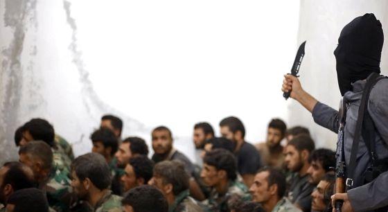 Un miembro del Estado Islámico blande un cuchillo junto a un grupo de soldados sirios capturados.