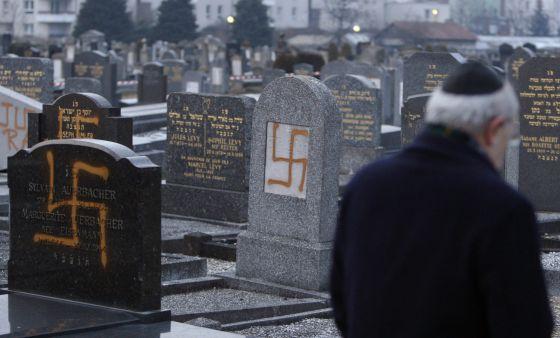 El líder de una comunidad judía examina tumbas pintadas con la cruz gamada en un cementerio cerca de Estrasburgo en 2010.