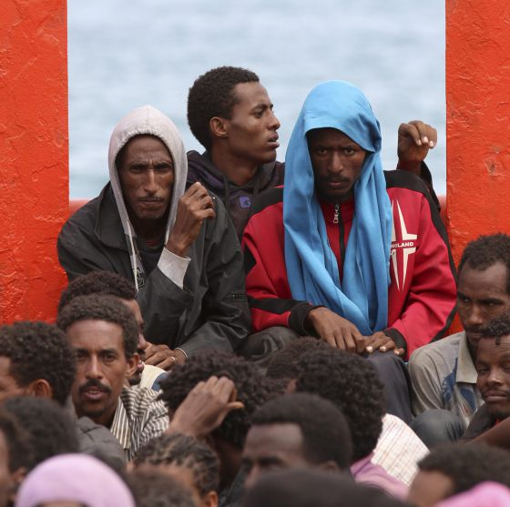 Un grupo de inmigrantes a bordo de un barco de la Armada italiana frente a Augusta en junio.