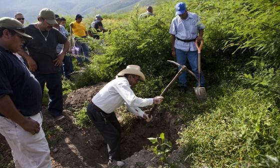Un hombre cava en una fosa en busca de los estudiantes desaparecidos.  SAÚL RUIZ