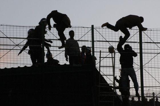 Inmigrantes subsaharianos saltando la valla de Melilla en presencia de agentes de la Guardia Civil el pasado mes de mayo.