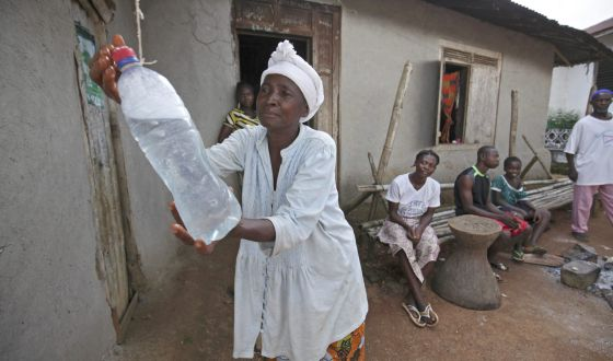 Una mujer se lava las manos con agua clorada, una medida de prevención ante el ébola, en Sierra Leona