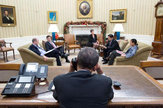 Barack Obama habla con Raúl Castro en el despacho Oval, en presencia de Ben Rhodes y Ricardo Zúñiga, entre otros.rn