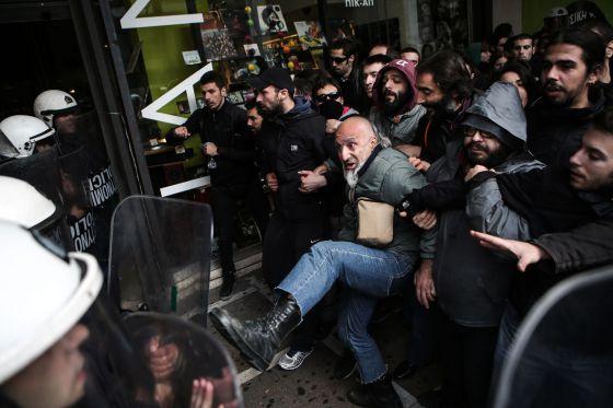 Manifestantes contra la apertura comercial en domingos se enfrentan a antidisturbios en Atenas.