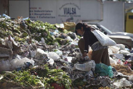 Una mujer busca comida en la Central de Abastos de la capital.