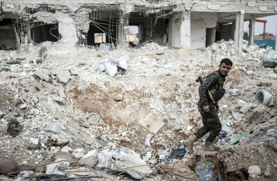 Un combatiente kurdo camina entre los escombros de un edificio en el centro de la ciudad siria de Kobane, este miércoles.