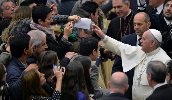 El papa Francisco recibe una carta de una mujer durante la audiencia general de los miércoles.