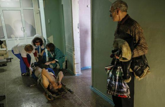 Tres sanitarias atienden en un hospital a un hombre herido, este domingo en la localidad ucrania de Artemivsk.