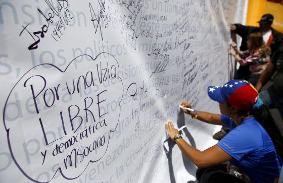 Varios opositores escriben en un mural, en una protesta el 28 de febrero en Caracas.
