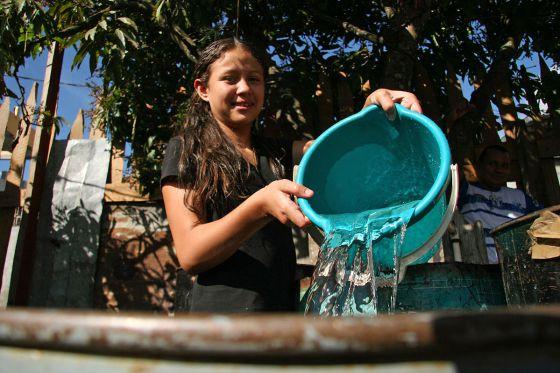 Una niña llena un recipiente de agua en Honduras.