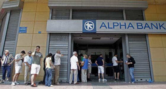 Varias personas hacen cola para sacar dinero en efectivo en un par de cajeros de Atenas
