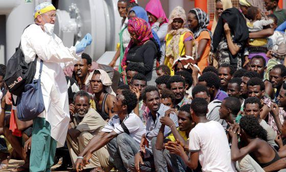 Inmigrantes esperan a desembarcar en el puerto siciliano de Pozzallo, el domingo.