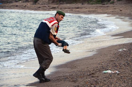 Un policía traslada el cadáver de un niño en una playa de Turquía.