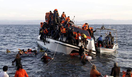 Refugiados, la mayoría sirios, tratan de abandonar un barco semihundido en la isla griega de Lesbos