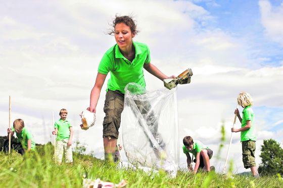 Niños recogiendo basura en un parque