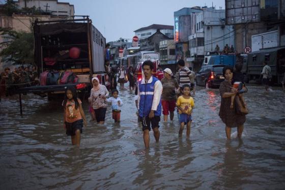 Vecinos de Yakarta caminan por una calle inundada en enero de 2014