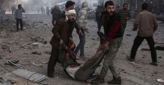 Dos sirios trasladan a una víctima de un bombardeo en Damasco