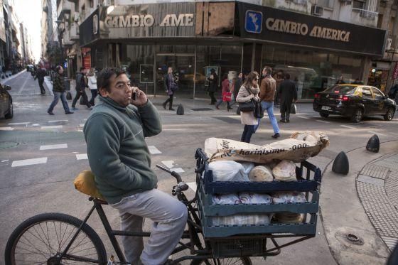 Un vendedor ambulante de comida se detiene frente a una casa de cambio del centro financiero de Buenos Aires.