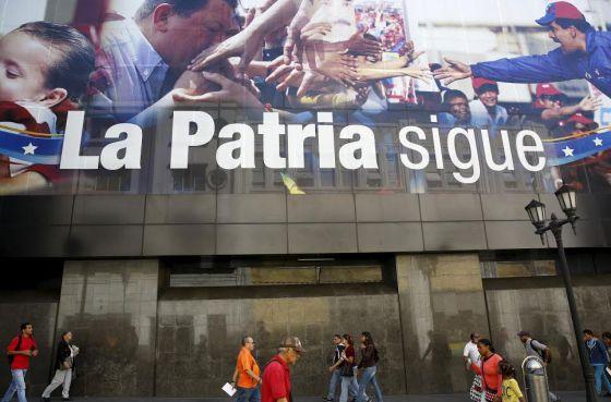 Ciudadanos de Caracas caminan este miércoles frente a un cartel que retrata a Chávez y Maduro cerca de la Asamblea Nacional