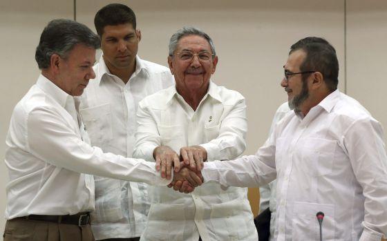 Juan Manuel Santos y Timochenko, líder de las FARC, se dan la mano en La Habana ante el líder cubano Raúl Castro, el pasado septiembre.