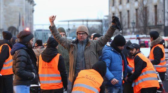 Miembros de seguridad cachean a un ciudadano antes de las celebraciones junto a la puerta de Brandenburgo hoy.