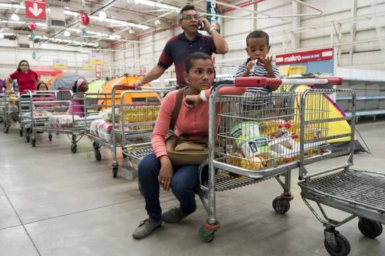 Un venezolano habla por su móvil mientras espera en la cola del supermercado.