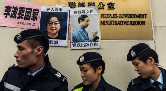 Policías junto a carteles de dos desaparecidos, el domingo en Hong Kong.