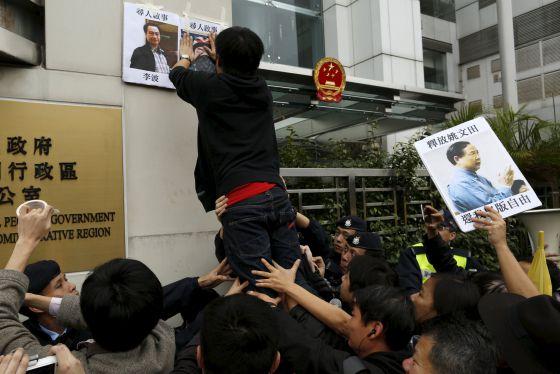Un activista coloca un cartel ante la oficina de representación china en Hong-Kong con los rostros de los editores desaparecidos Lee Bo y Lu Bo.