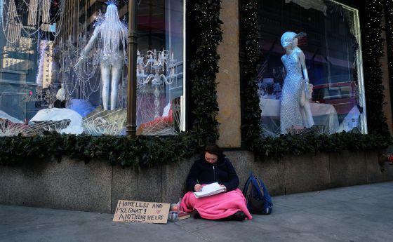 Uma mulher pede esmola na Quinta Avenida.