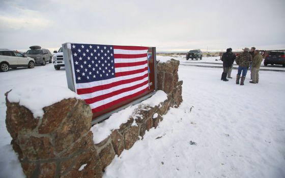 Los manifestantes han cubierto la señal del refugio con la bandera de Estados Unidos.