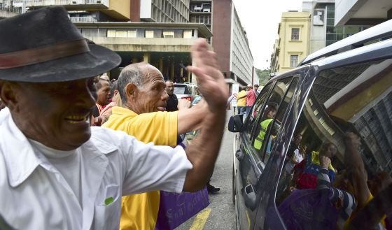 Pro-government supporters hit the car of Henry Ramos Allup, the newly elected president of the National Assembly.