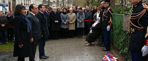 Hidalgo, Hollande y Valls observan un minuto de silencio ante la placa que recuerda el asesinato del policía en la matanza de enero de 2015 en París.