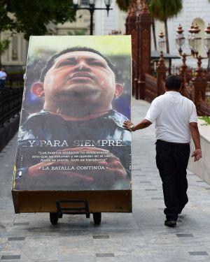 Operarios retiran ayer carteles del expresidente venezolano Hugo Chávez en la Asamblea.