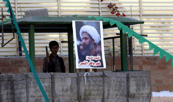 Un miliciano Huthi hace guardia junto al póster del clérigo chií ejecutado durante una manifestación contra Arabia Saudí, este jueves en Yemen.