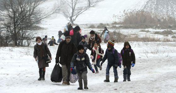 Varios migrantes se dirigen a un campamento de recepción temporal en Miratovac, en la frontera de Serbia y Macedonia.