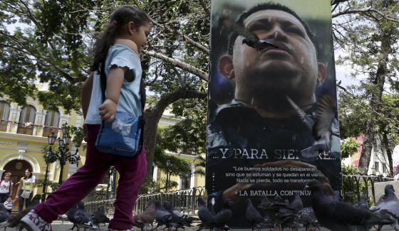 Una niña corre frente a un retrato del fallecido Hugo Chávez.