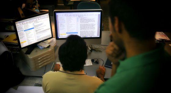 Un trabajador lee el correo electrónico en un ordenador de la oficina.