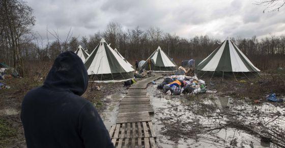 Un migrante camina hacia una de las viviendas del campo de Grande-Synthe (Francia).