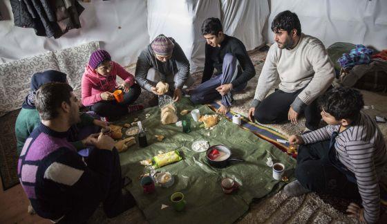 La familia yazidí de Arash Faramarzi, mientras almuerza en su tienda.