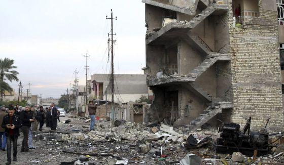 Un grupo de personas permanece en el lugar donde ayer explosionó un coche bomba, en Bagdad, Irak, el pasado 12 de enero.