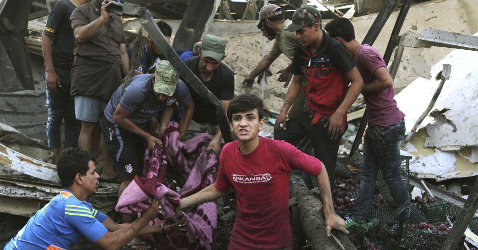 Un grupo de iraquíes saca un cadáver de los escombros en Irak
